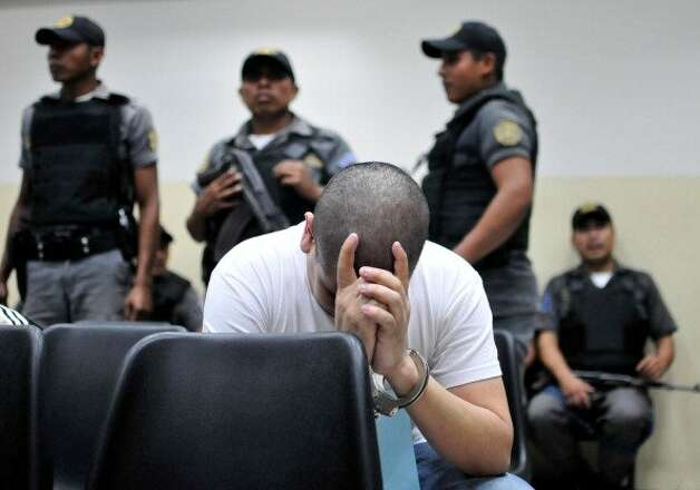 File: A suspected member (C) of the Mexican drug cartel 'Los Zetas' from Guatemala and Mexico is guarded as he waits in court for a judgement in Guatemala City on June 27, 2012. Over 30 people accused of belonging to the drug cartel Zetas were to be sentenced on various offenses, including murder, kidnapping and other crimes.  (Photo Luis SOTO/GettyImages) (AFP/Getty Images)