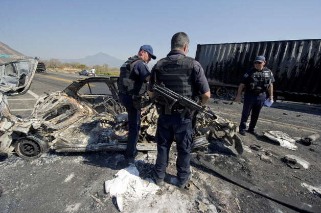 File: Mexican Federal Police officers inspect the charred wreckage of a car used to make a barricade blocking the Apatzingan-Uruapan road, Michoacan State, Mexico, on December 11, 2010. (Photo ALFREDO ESTRELLA/AFP/Getty Images) (AFP/Getty Images)