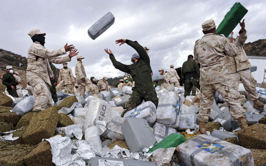 Mexican soldiers unload bundles of seized marijuana before incinerating the drugs at a military base in Tijuana, Mexico, on Wednesday, Oct. 20, 2010. Authorities carried out the biggest marijuana bust in Mexico's history this week when approximately 134 tons of marijuana headed for the U.S. were confiscated by soldiers and police. Mexico has impounded more than 7,400 tons of marijuana this year as part of President Felipe Calderon's fight against drug cartels. Photographer: David Maung/Bloomberg via Getty Images (Bloomberg via Getty Images)
