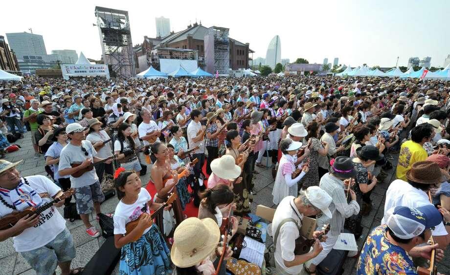 "These 2,134 ukulele players set a new record this July 28 in Yokohama, Japan, playing ""Aloha Mahalo A Hui Ho,"" by Hawaiian-born former sumo wrestler Konishiki. Photo: KAZUHIRO NOGI, AFP/Getty Images / k"