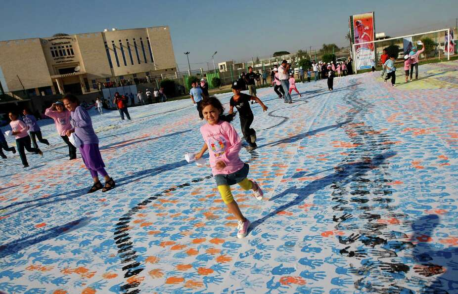 Palestinian children attempt to break the Guinness world record for the largest hand-print paint in