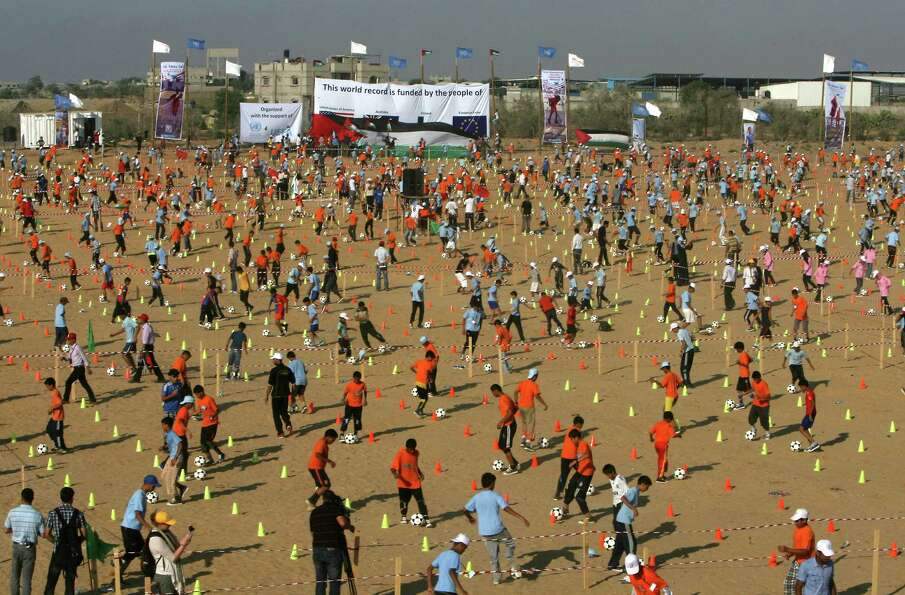 Here, thousands of Palestinian children try for the record in soccer ball dribbling in Rafah on July