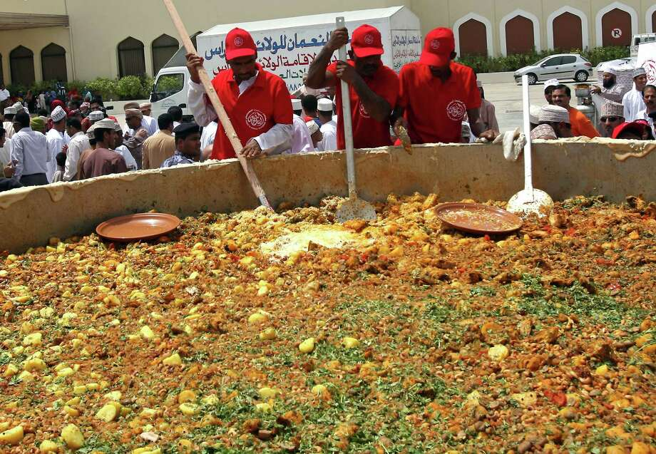 "Omani men stir ingredients in a large pot as they prepare the traditional ""Kabsa"" dish in an attempt to set a new Guinness world record in Muscat on July 23, 2010. Photo: MOHAMMED MAHJOUB, AFP/Getty Images"