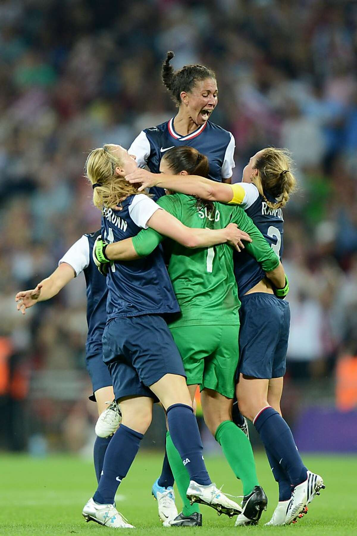 LONDON, ENGLAND - AUGUST 09: Hope Solo #1, Shannon Boxx #7 and Christie Rampone of the United States celebrates after defeating Japan by a score of 2-1 to win the Women's Football gold medal match on Day 13 of the London 2012 Olympic Games at Wembley Stadium on August 9, 2012 in London, England. (Photo by Michael Regan/Getty Images)