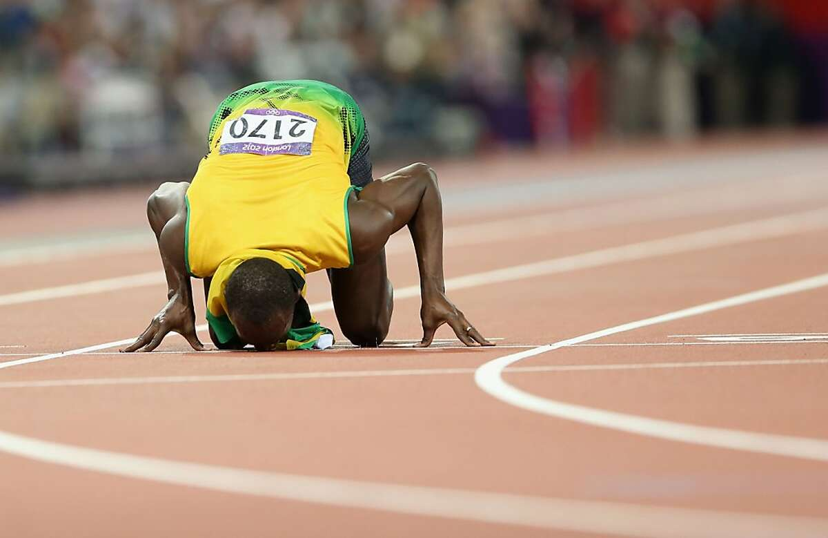 LONDON, ENGLAND - AUGUST 09: Usain Bolt of Jamaica kisses the finish line as he celebrates after winning gold in the Men's 200m Final on Day 13 of the London 2012 Olympic Games at Olympic Stadium on August 9, 2012 in London, England. (Photo by Streeter Lecka/Getty Images)