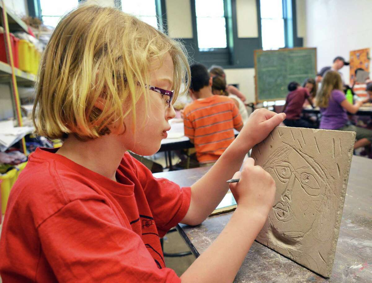 Seven-year-old Madeline Epping of East Greenbush works on a self portrait relief carving at summer arts camp at the Arts Center of the Capital Region in Troy Wednesday July 25, 2012. (John Carl D'Annibale / Times Union)