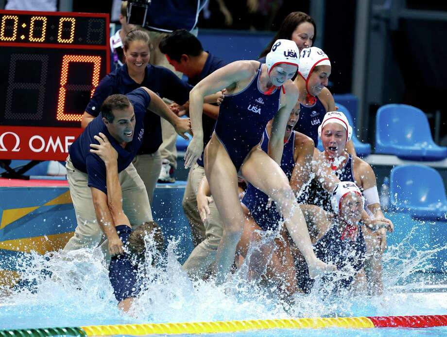 United States coach Adam Krikorian, left, is pulled into the pool moments after the team beat Spain during the gold medal women's water polo match at the 2012 Summer Olympics, Thursday, Aug. 9, 2012, in London. (AP Photo/Julio Cortez) Photo: Julio Cortez, Associated Press / AP