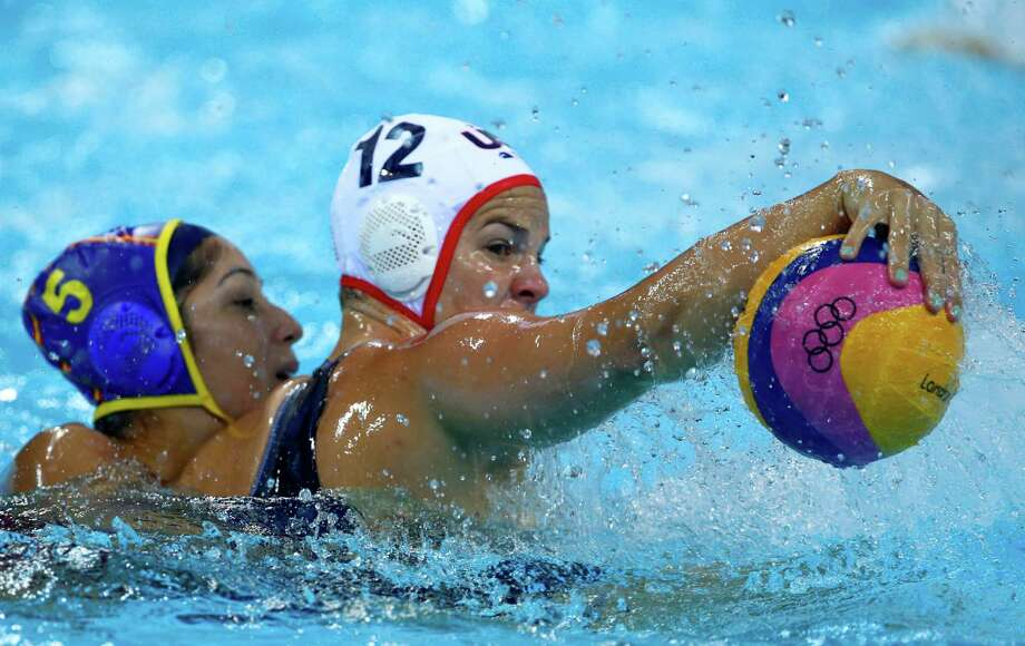 Kami Craig, right, of the United States attacks against Matilde Ortiz Reyes of Spain during the gold medal women's water polo match at the 2012 Summer Olympics, Thursday, Aug. 9, 2012, in London. (AP Photo/Julio Cortez) Photo: Julio Cortez, Associated Press / AP