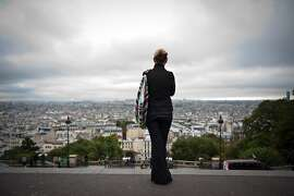 A woman enjoys the view of Paris from the Sacre Coeur basilica esplanade, on September 24, 2010 in Paris.