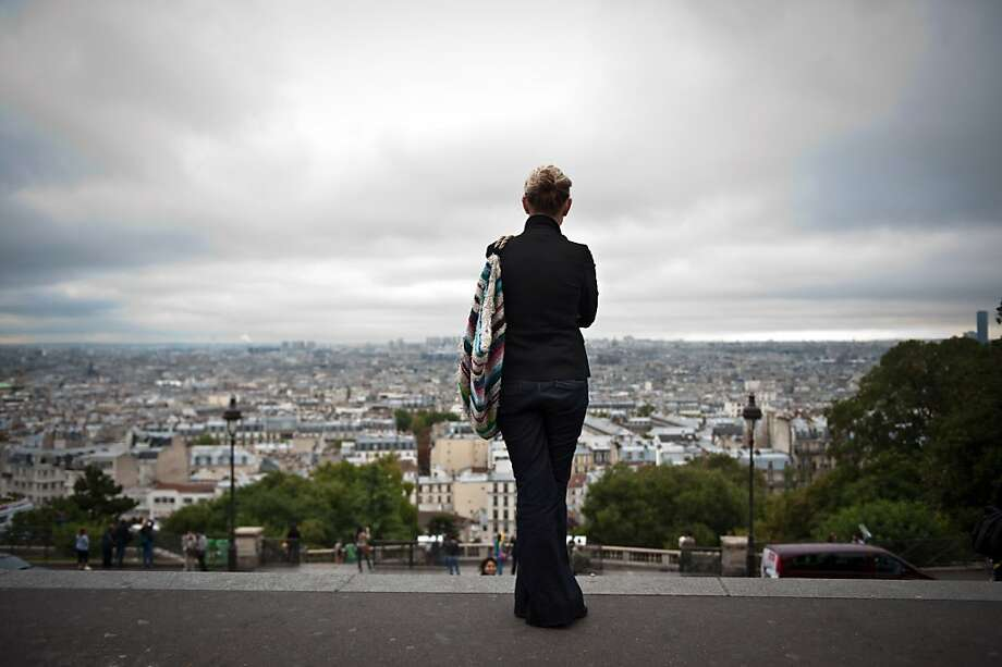 A woman enjoys the sight of Paris from the Sacré Coeur Basilica esplanade in Montmartre. Photo: Martin Bureau, AFP/Getty Images
