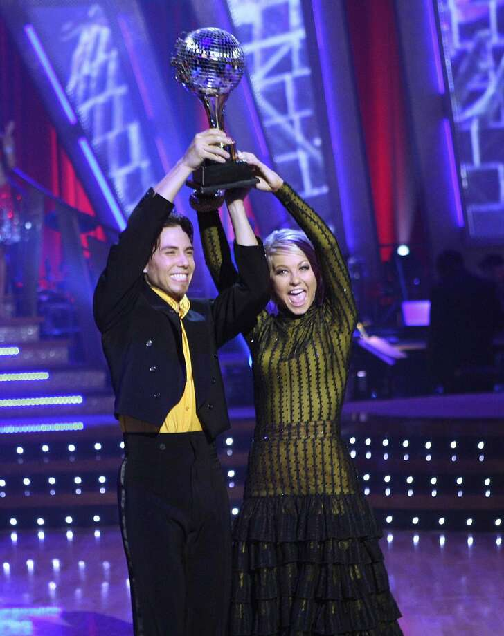 "Olympic gold medal-winning speed skater Apolo Anton Ohno , left, who was crowned champion and awarded the mirror ball trophy with his professional partner, Julianne Hough, on the season finale of  ""Dancing with the Stars."" (CAROL KAELSON / Associated Press)"