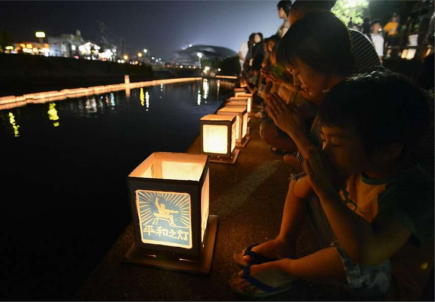 A woman and a boy pray next to lanterns along a river, paying tribute to the victims of the atomic b