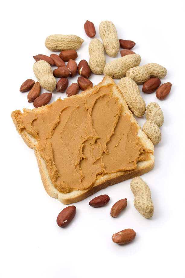 Slice of bread with peanut butter spread isolated on wihte. PEANUTS PEANUT SHELLS Photo: Igor Dutina / handout / stock agency