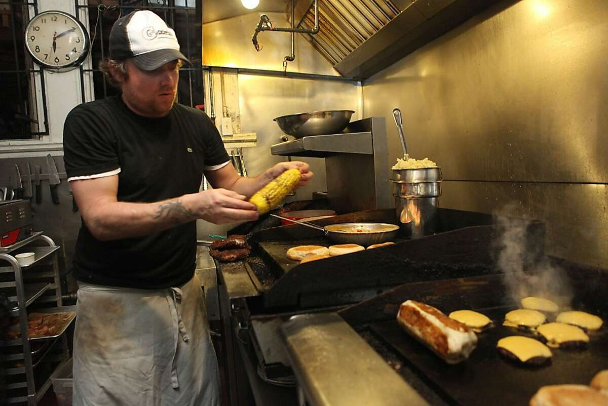 Co-owner and chef Shane LaValley getting corn as bacon burgers and a summer tuna wrap are being cooked at the Broken Record Kitchen in San Francisco, Calif., on Tuesday, August 7, 2012.