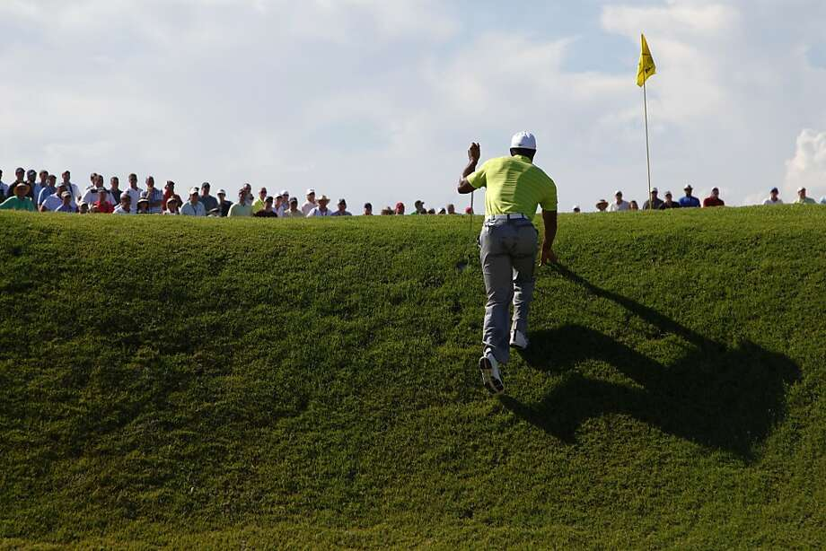 Tiger Woods climbs out of a bunker on the 14th hole, one of three he bogeyed in his opening round. Photo: Chuck Burton, Associated Press
