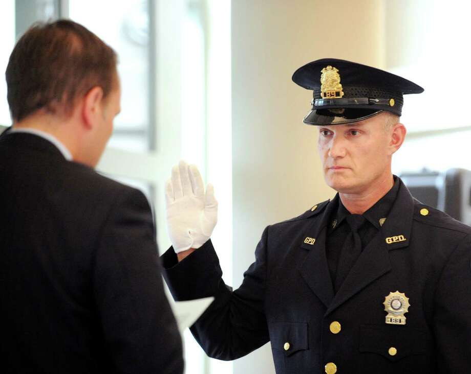 Greenwich First Selectman Peter Tesei, left, swears in Greenwich Police Officer Alton Hall as a sergeant during a promotion ceremony for Hall and  Lt. James Bonney at Greenwich Police Headquarters, Thursday, Aug. 9, 2012. Photo: Bob Luckey / Greenwich Time