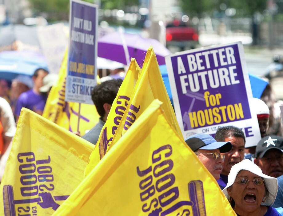 Protesters march down Louisiana Street last month in support of Houston janitors' wage demands. On Saturday, the janitors are expected to vote to ratify a tentative agreement reached this week with six of the city's largest cleaning companies. Photo: Cody Duty / © 2011 Houston Chronicle
