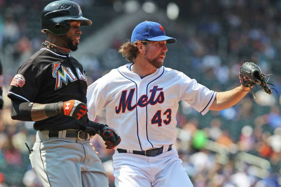 New York Mets starting pitcher R.A. Dickey, right, beats Miami Marlins' Jose Reyes to first base for an out during the eighth inning of the baseball game Thursday, Aug. 9, 2012 at Citi Field in New York. The Mets beat the Marlins 6-1. (AP Photo/Seth Wenig). Photo: Seth Wenig