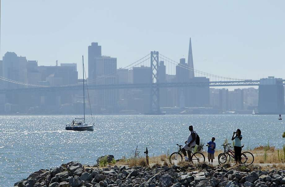 Lyle Scott with kids, Landen and Layla, cools off near the bay at Oakland's Middle Harbor Shoreline Park. Photo: Carlos Avila Gonzalez, The Chronicle