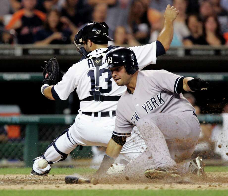 New York Yankees' Nick Swisher scores from second base on a single by Mark Teixeira as Detroit Tigers catcher Alex Avila (13) drops the ball in the eighth inning of a baseball game, Wednesday, Aug. 8, 2012, in Detroit. The Yankees won 12-8. (AP Photo/Duane Burleson) Photo: Duane Burleson