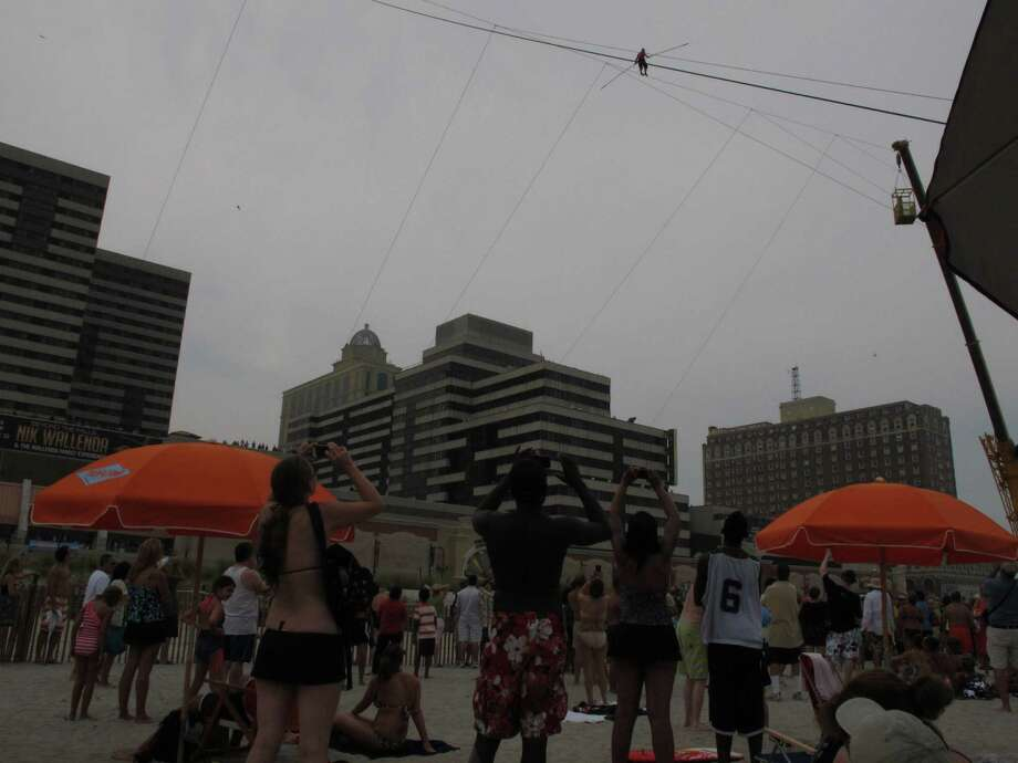 A crowd watches as daredevil Nik Wallenda walks a tightrope above the beach at Atlantic City on Thursday, Aug. 9, 2012. Officials say some 150,000 people witnessed the walk. (AP Photo/Geoff Mulvihill) Photo: Geoff Mulvihill / AP