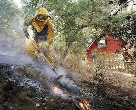 A firefighter works to put out a spot fire near a home along Parkhill Road East of Santa Margarita, Calif. Monday, July 16, 2012. A wildfire threatened more than 50 homes Tuesday in Central California, as firefighters made progress against another blaze that scorched coastal brush on a Southern California Marine base.