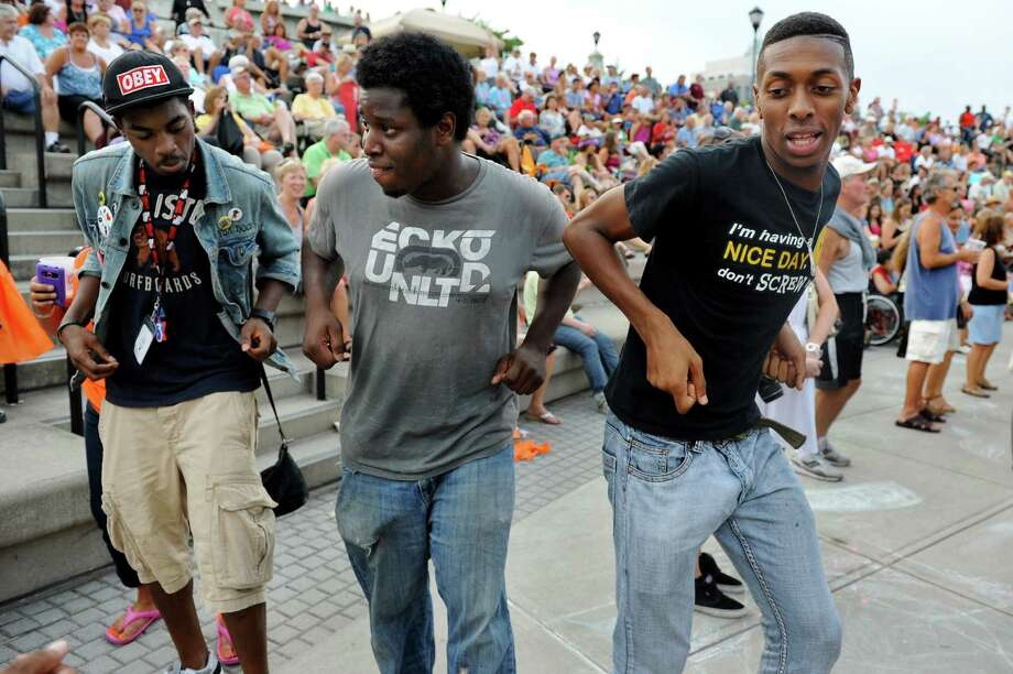 Denzel Caldwell of Troy, left, Lavaughn Stewart of Latham, center, and Ewart Simpson of Albany dance to the music of the Beach Bums: A Tribute to The Beach Boys during the final concert of the Alive at Five series on Thursday, Aug. 9, 2012, at Riverfront Park in Albany, N.Y. (Cindy Schultz / Times Union) Photo: Cindy Schultz / 00018796A