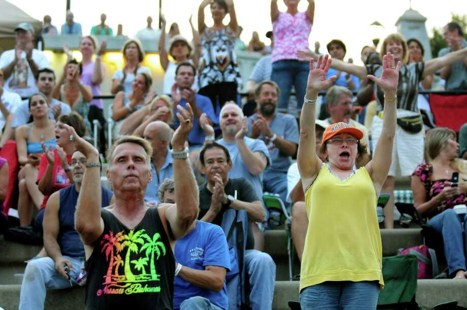 Don Raux of Clifton Park, left, and Resa Tanner of Colonie, right, join the audience as they cheer for the Beach Bums: A Tribute to The Beach Boys performs during the final concert of the Alive at Five series on Thursday, Aug. 9, 2012, at Riverfront Park in Albany, N.Y. (Cindy Schultz / Times Union) Photo: Cindy Schultz / 00018796A