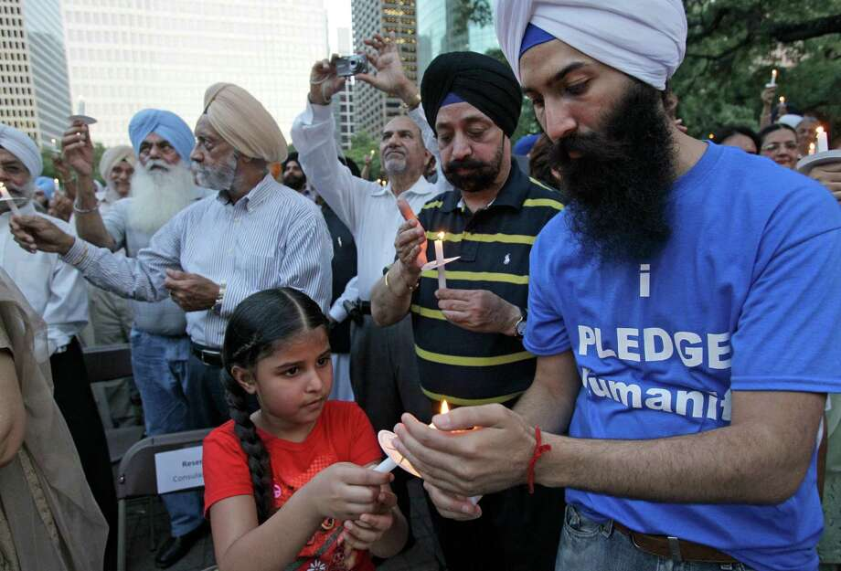 Simjeet Kaur, 5, lights her candle from Supreet Singh, right, during a candlelight vigil Thursday, Aug. 9, 2012, in Houston outside City Hall to remember the victims of the Sikh temple shooting in Wisconsin. Photo: Melissa Phillip, Houston Chronicle / © 2012 Houston Chronicle