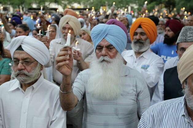 A crowd of people raise their candles during vigil Thursday, Aug. 9, 2012, in Houston  at the reflection pool at City Hall to remember the victims of the Sikh temple shooting in Wisconsin. Photo: Melissa Phillip, Houston Chronicle / © 2012 Houston Chronicle
