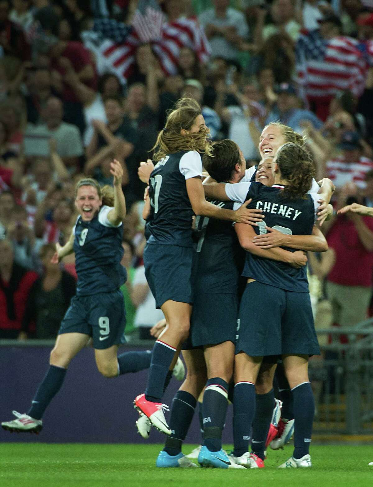 Tobin Heath (17), Sydney Leroux (11) Lauren Cheney (12), Amy Rodriguez (8) and United States' Heather O'Reilly (9) race in to mob Carli Lloyd, facing, of the United States after the women's soccer gold medal match against Japan at the 2012 London Olympics on Thursday, Aug. 9, 2012. The USA won the game 2-1 to claim the gold medal. Lloyd scored both goals for the Americans. ( Smiley N. Pool / Houston Chronicle )