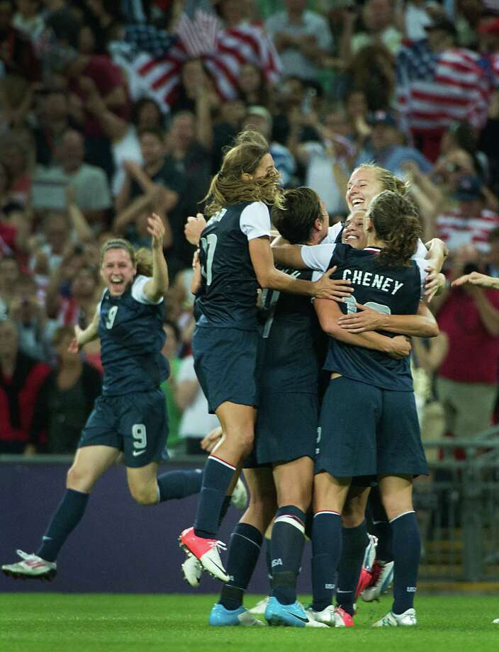 Tobin Heath (17), Sydney Leroux (11) Lauren Cheney (12), Amy Rodriguez (8) and United States' Heather O'Reilly (9) race in to mob Carli Lloyd, facing, of the United States after the women's soccer gold medal match against Japan at the 2012 London Olympics on Thursday, Aug. 9, 2012. The USA won the game 2-1 to claim the gold medal.  Lloyd scored both goals for the Americans. ( Smiley N. Pool / Houston Chronicle ) Photo: Smiley N. Pool / © 2012  Houston Chronicle