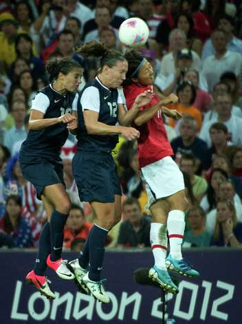 United States' Rachel Buehler (16) and Lauren Cheney (12) fight for a header against Japan's Yuki Ogimi during the women's soccer gold medal match at the 2012 London Olympics on Thursday, Aug. 9, 2012. The USA won the game 2-1 to claim the gold medal. Photo: Smiley N. Pool, Houston Chronicle / © 2012  Houston Chronicle