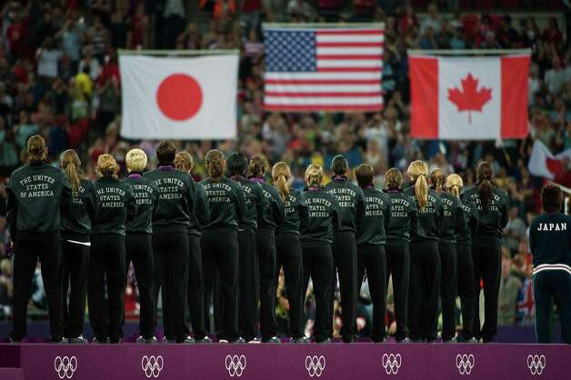 US players stand on the awards podium for their national anthem as the flags are raised following the women's soccer gold medal match at the 2012 London Olympics on Thursday, Aug. 9, 2012. The USA defeated Japan the game 2-1 to claim the gold medal. Canada took the bronze. Photo: Smiley N. Pool, Houston Chronicle / © 2012  Houston Chronicle