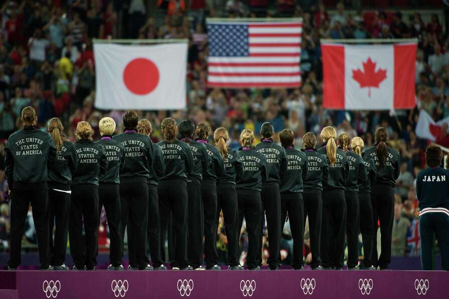 US players stand on the awards podium for their national anthem as the flags are raised following th