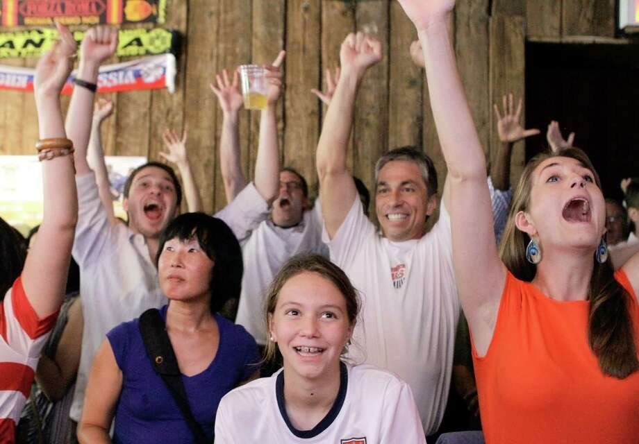 People react as they watch a television broadcast of the United States women's soccer team taking on Japan in the gold medal match at the 2012 London Summer Olympics, Thursday, Aug. 9, 2012, at Nevada Smiths bar in New York. The U.S. won 2-1. Photo: Alex Katz
