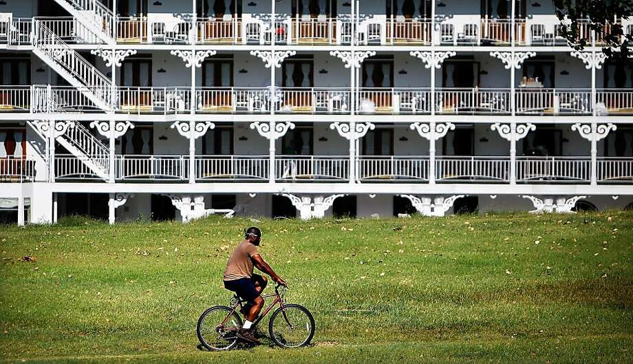 On his morning bike ride along the River at Mississippi Greenbelt Park in Memphis, Tenn., Selwyn Ballard passes the American Queen Thursday August 9, 2012. Low water has forced the American Queen to dock on the north side of Mud Island till it can continue its voyage to Vicksburg, Miss. Photo: Jim Weber, Associated Press