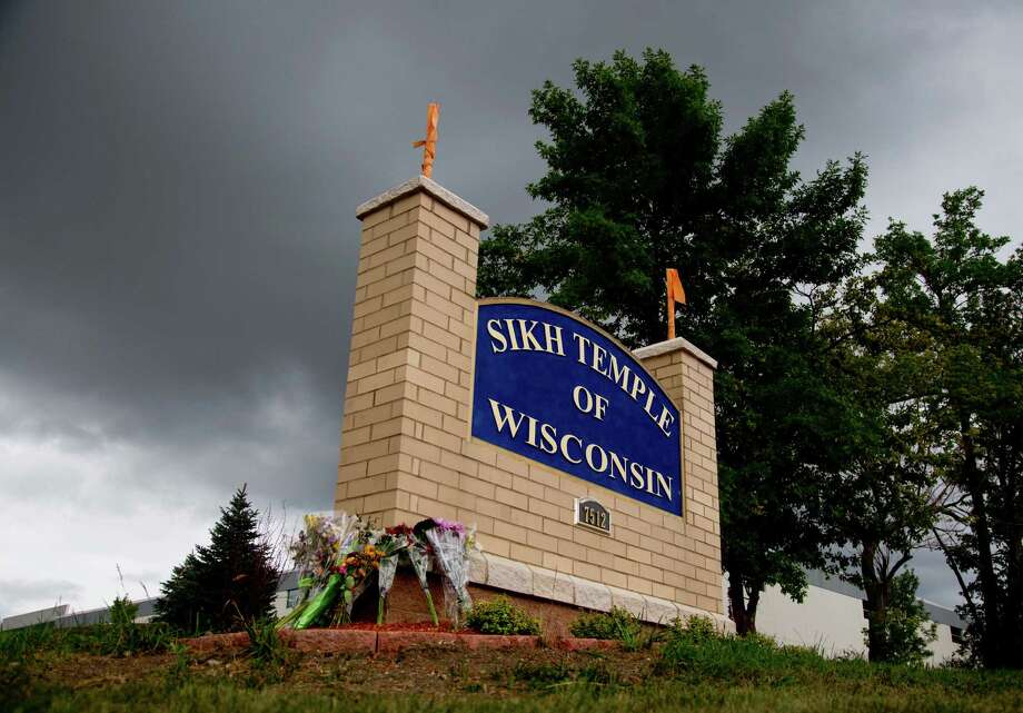 Flowers lie on the sign to the Sikh temple of Wisconsin where members were allowed to re-enter for the first time in Oak Creek, Wis., Thursday, Aug 9, 2012.  The mass shooting last Sunday claimed six members of the temple. (AP Photo/Jeffrey Phelps) Photo: JEFFREY PHELPS