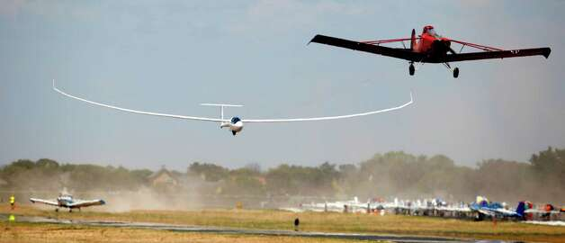 An open class glider is pulled into the air Wednesday Aug. 8, 2012 at Garner Field airport in Uvalde by a Piper Pawnee tow plane as the glider starts Day 4 of competition at the 32nd FAI World Gliding Championship. Open class gliders are not restricted in their design and are most noted for their extremely long, slender wings. Photo: William Luther, San Antonio Express-News / © 2012 San Antonio Express-News