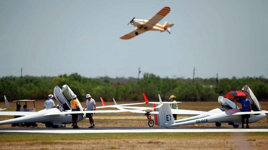 Gliders wait on the runway Wednesday Aug. 8, 2012 to be towed into the air at Garner Field airport in Uvalde at the start Day 4 of competition at the 32nd FAI World Gliding Championship as a tow plane flies in the background. Photo: William Luther, San Antonio Express-News / © 2012 San Antonio Express-News
