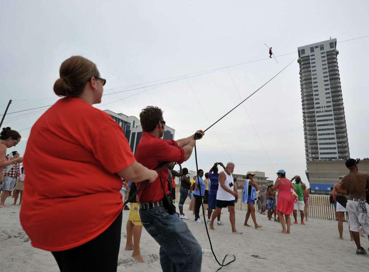 Volunteers hold ropes to steady the wire during daredevil Nik Wallenda's 1,500-foot (457 meters) tightrope walk 100 feet (30.5 meters) above the beach August 9, 2012 in Atlantic City, New Jersey. AFP PHOTO/Stan HONDASTAN HONDA/AFP/GettyImages