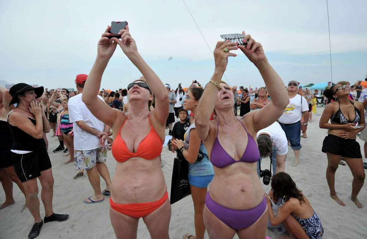 Jesie DeMarco (L) and cousing Noreen Saggese (R) take photographs of daredevil Nik Wallenda during his 1,500-foot (457 meters) tightrope walk 100 feet (30.5 meters) above the beach August 9, 2012 in Atlantic City, New Jersey. AFP PHOTO/Stan HONDASTAN HONDA/AFP/GettyImages