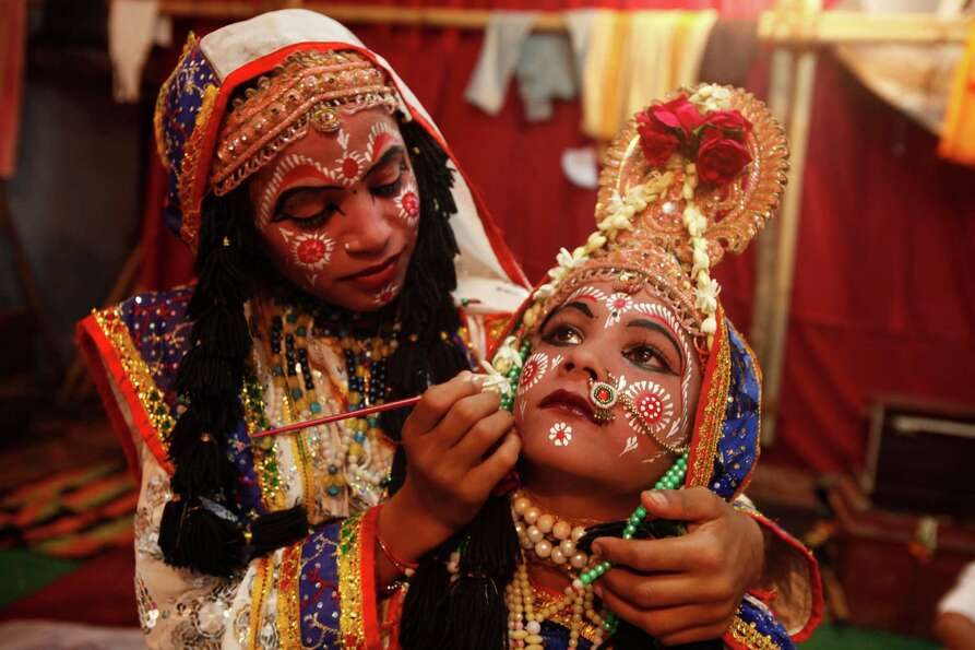 A Young Indian Girl Applies Makeup To Another Girl Before
