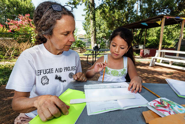 Stacey Merkt, left, watches as Aracely Moreno, a second-grader at Crockett Elementary, records measurements taken from her basil plant. Photo: MARVIN PFEIFFER, STAFF / Express-News 2012