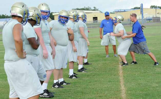 CoachMarcus Zarosky, right, gives instructions to his players as he demonstrates the stance he wants them to hold as they go through  a drill.  Hamshire-Fannett held one of their football practices Wednesday night, August 8, 2012 and started at 6 p.m.   Dave Ryan/The Enterprise Photo: Dave Ryan