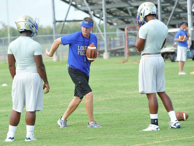 New Head Coach Kane Harris, middle,  gives instructions to his quarterbacks during the practice.  Hamshire-Fannett held one of their football practices Wednesday night, August 8, 2012 and started at 6 p.m.   Dave Ryan/The Enterprise Photo: Dave Ryan