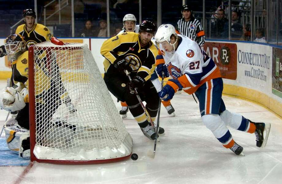 Sound Tigers' #27 Matt Martin tries to bring the puck around the backside of the goal with Providence's #7 Andy Wozniewski looking to block, during hockey action in Bridgeport, Conn. on Wednesday Dec. 02, 2009. Photo: Christian Abraham / Connecticut Post