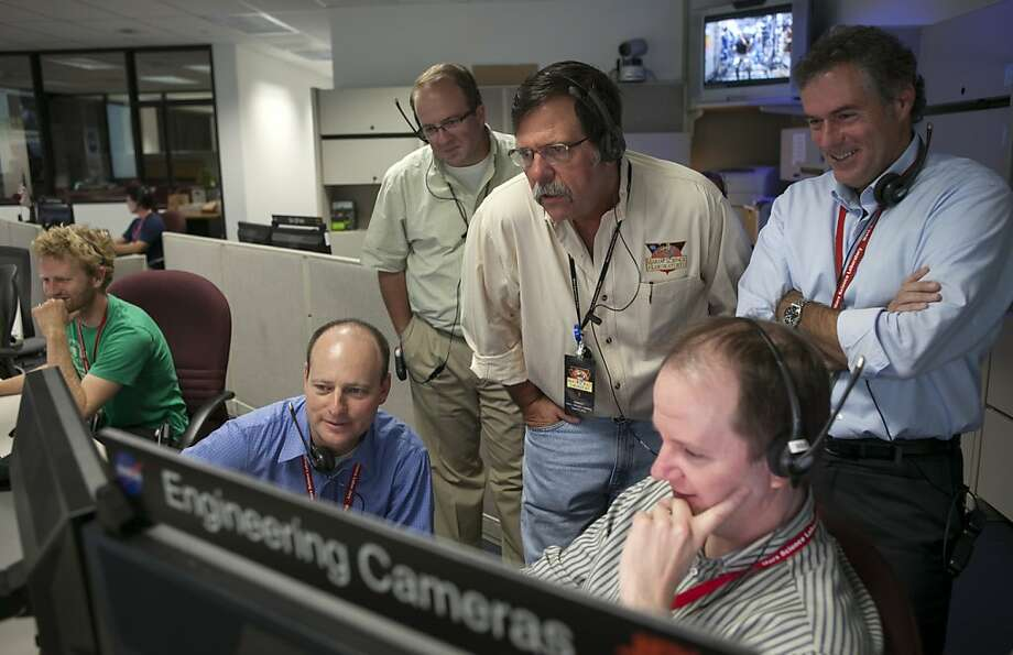 NASA engineers look at the first images from Curiosity rover's just-activated cameras. Photo: Damian Dovarganes, Associated Press