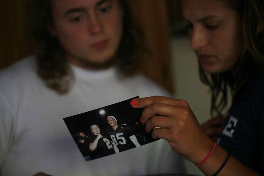 Daniel Dewitt's former classmate and teammate Wes Moyer and his friend Sarah Guzick pull out a photo of Wes and Daniel, who was a tight end and defensive end at Alameda High. Photo: Mike Kepka, The Chronicle