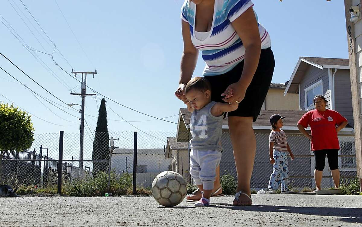 Selene Rico holds her son Aythan, 9 months, with Roberto Perez, 7 years old, Wednesday Aug. 8, 2012, in Richmond, Calif. They saw the smoke and say they heard an explosion at the Chevron refinery from their home directly across from the freeway Monday evening.